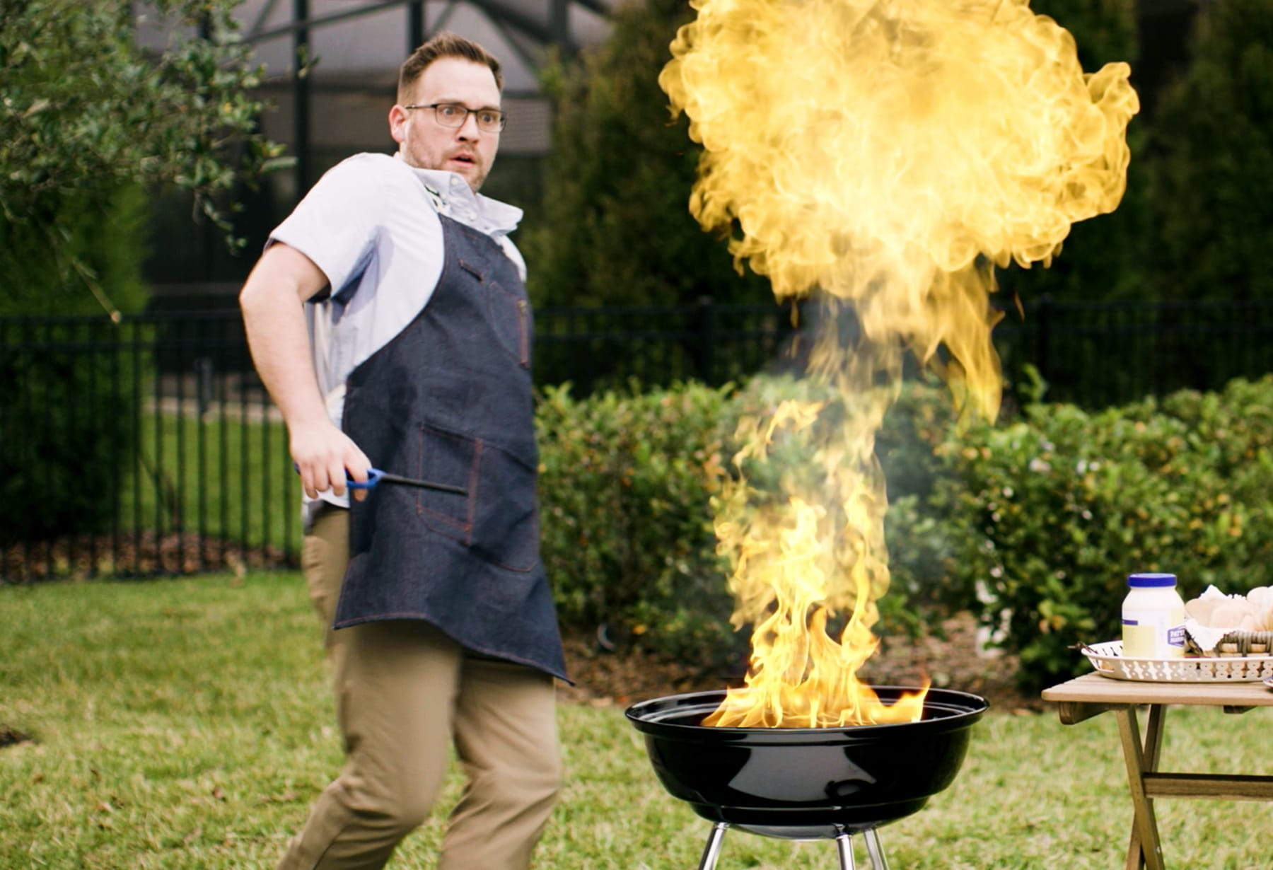 Photo of a man jumping away from an exploding barbecue grill