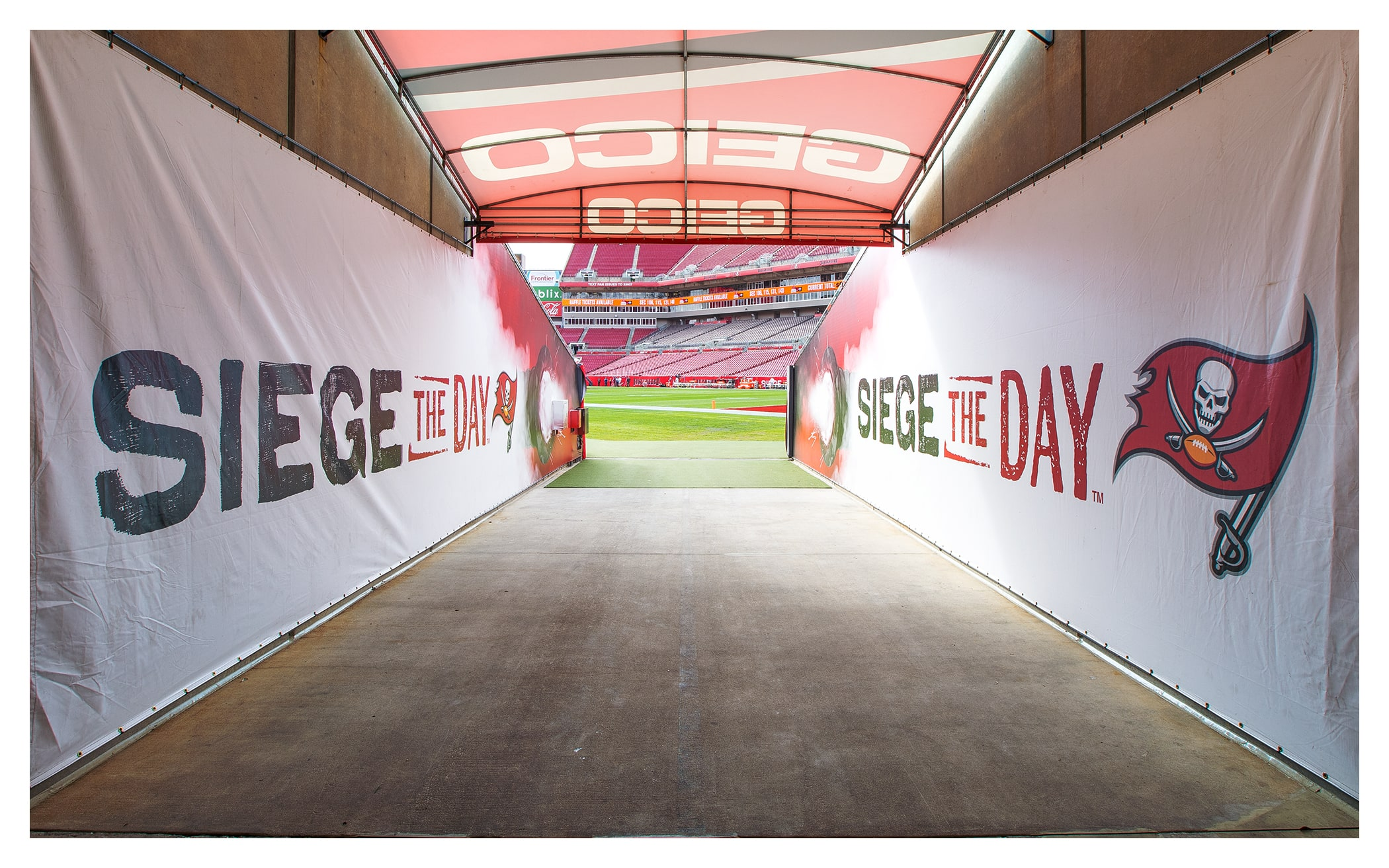 Photo of tunnel leading out on to the field with Siege the Day banners on the walls